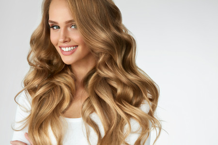 Photo pour Beautiful Curly Hair. Smiling Girl With Healthy Wavy Long Blonde Hair. Portrait Happy Woman With Beauty Face, Sexy Makeup And Perfect Hair Curls. Volume, Hairstyle, Hairdressing Concept. High Quality - image libre de droit