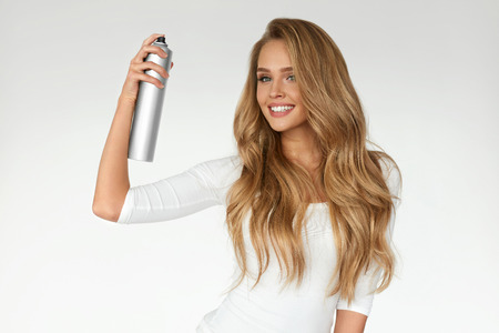 Photo pour Hairstyle. Woman Spraying Hairspray On Beautiful Long Curly Hair On White Background. Attractive Smiling Girl With Blonde Shiny Wavy Hair Using Spray For Styling, Hairdressing. Beauty. High Resolution - image libre de droit