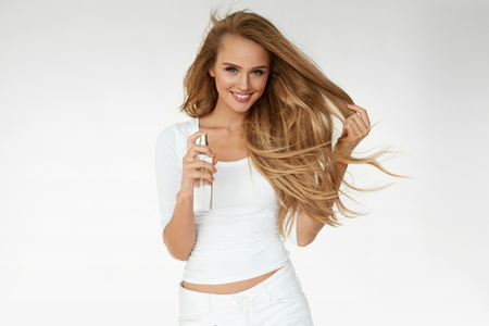 Photo pour Hair Cosmetics. Smiling Woman With Healthy Beautiful Long Wavy Hair Applying Thermal Protect Hair Spray. Happy Girl With Blonde Smooth Hair Using Heat Protect Spray. Haircare Cosmetic. High Resolution - image libre de droit