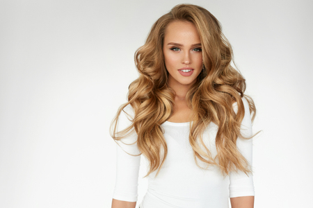 Foto de Beautiful Curly Hair. Smiling Girl With Healthy Wavy Long Blonde Hair. Portrait Happy Woman With Beauty Face, Sexy Makeup And Perfect Hair Curls. Volume, Hairstyle, Hairdressing Concept. High Quality - Imagen libre de derechos