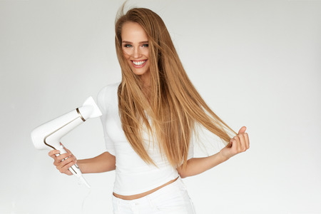 Photo pour Hair Dryer. Beautiful Smiling Woman Drying Healthy Long Straight Hair Using Hairdryer. Portrait Attractive Happy Girl With Blonde Hair Doing Hairstyle. Hairdressing, Hair Care Concept. High Resolution - image libre de droit