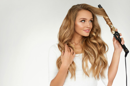 Photo pour Curly Hair. Beautiful Smiling Woman With Long Blonde Wavy Hair Ironing It, Using Curling Iron. Happy Girl With Gorgeous Healthy Smooth Hair Using Curler For Perfect Curls. Hairstyle And Hairdressing - image libre de droit