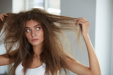Foto de Damaged Hair. Beautiful Sad Young Woman With Long Disheveled Hair. Closeup Portrait Of Female Model Holding Messy Unbrushed Dry Hair In Hands. Hair Damage, Health And Beauty Concept. High Resolution - Imagen libre de derechos