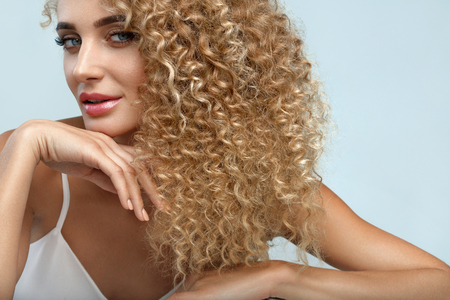 Photo pour Perfect Hair. Beautiful Woman Model With Long Healthy Blonde Curly Hair. Portrait Gorgeous Sexy Girl With Natural Facial Makeup, Beauty Face And Fashion Hairstyle. Hair Care Cosmetics. High Resolution - image libre de droit