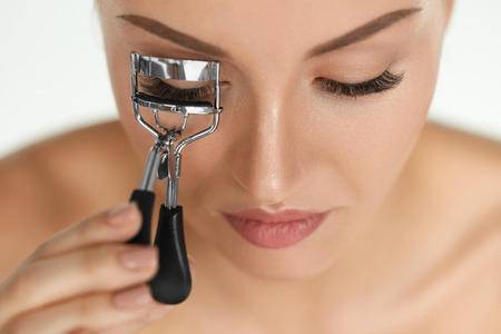Photo pour Beauty Makeup. Closeup Of Beautiful Female Model Face With Professional Natural Make-up And Smooth Soft Skin. Young Woman Using Eyelash Curler On Long Eyelashes. Curly Eye Lashes. High Resolution - image libre de droit