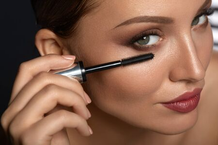 Beauty Woman Makeup. Closeup Of Beautiful Woman Applying Black Mascara On Eyelashes. Portrait Of Female Model With Smooth Healthy Skin, Sexy Make-up Using Cosmetic Brush On Eye Lashes. High Resolution