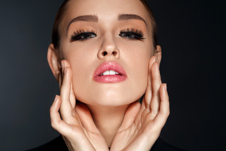 Foto de Perfect Face Makeup. Closeup Portrait Of Beautiful Sexy Woman With Professional Makeup Touching Her Smooth Soft Healthy Facial Skin. Glamorous Female Model With Long Black Eyelashes. High Resolution - Imagen libre de derechos