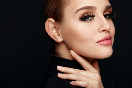 Photo pour Beauty Makeup. Closeup Of Beautiful Smiling Woman Touching Soft Smooth Facial Skin. Portrait Of Sexy Young Female Model With Professional Make-up And Long Black Eyelashes. Cosmetics. High Resolution - image libre de droit