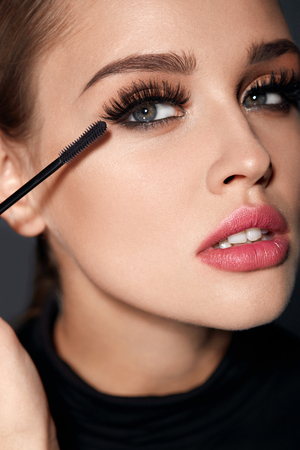 Long Black Eyelashes. Closeup Of Beautiful Sexy Girl With Mascara Brush Near Face. Glamorous Woman With Perfect Face Makeup, Long Thick Eye Lashes Applying Cosmetics. Beauty Concept. High Resolution