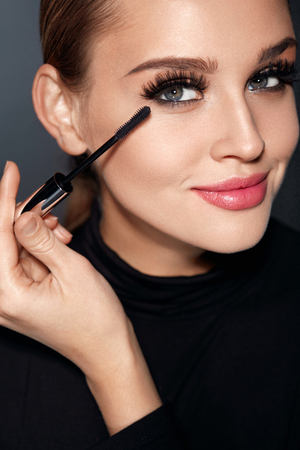 Photo for Beauty Makeup And Cosmetics. Closeup Of Beautiful Woman Face With Soft Skin, Perfect Professional Facial Make-up Applying   Black Mascara On Long Thick Eyelashes With Cosmetic Brush. High Resolution - Royalty Free Image
