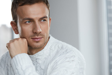 Foto de Handsome Young Man With Beautiful Face, Smooth Soft Facial Skin And Stubble Beard. Portrait Attractive Male Model In White Sweater Indoors. Beauty, Skin Care And Man's Health Concepts. High Resolution - Imagen libre de derechos