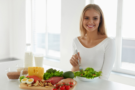 Foto de Nutrition. Beautiful Woman On Healthy Diet With Organic Green Vegetable Salad In Kitchen. Smiling Girl Sitting At Table With Different Food Ingredients, Variety Of Foods And Products. High Resolution - Imagen libre de derechos