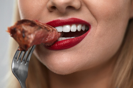 Photo pour Eating Meat. Closeup Of Woman Mouth With Red Lips, White Teeth Biting Tasty Beef Steak On Fork. Close-up Of Beautiful Female Mouth Eating Delicious Grilled Meat. Nutrition Concept. High Resolution - image libre de droit