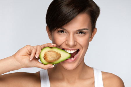 Photo pour Diet Nutrition. Beautiful Smiling Woman Biting Organic Green Avocado. Happy Vegetarian Girl With Soft Skin, Fresh Natural Face Makeup Eating Avocado. Healthy Lifestyle, Health Concept. High Resolution - image libre de droit