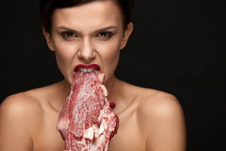 Photo pour Eating Meat. Hungry Woman With Red Lips Going To Eat Raw Meat. Portrait Of Girl With Beautiful Face Makeup Biting Beef Steak Meat With Her Teeth. High Protein Diet And Food Concept. High Resolution - image libre de droit