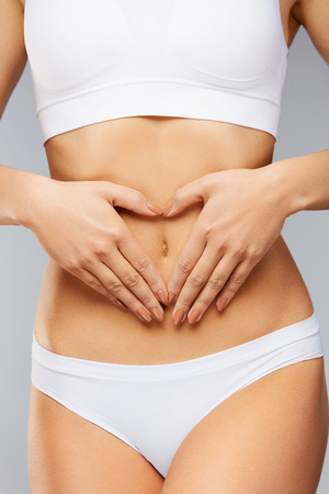 Foto de Female Health Care. ?loseup Healthy Young Woman With Beautiful Fit Slim Body, Perfect Smooth Soft Skin In White Panties Holding Hands On Stomach. Good Digestion, Women Health Concept. High Resolution - Imagen libre de derechos