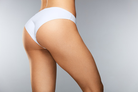 Photo pour Body Care. Beautiful Slim Woman Back With Tight Firm Buttocks, Sexy Butt, Healthy Soft Skin In White Bikini Panties. Closeup Girl With Perfect Body Shape In Underwear. Beauty Concept. High Resolution - image libre de droit