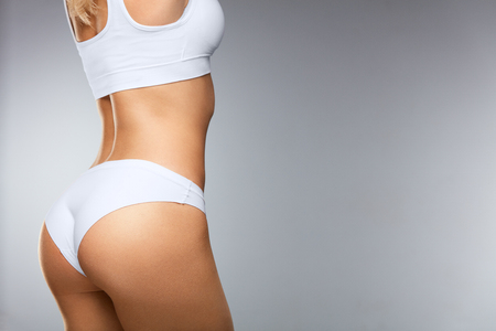 Foto de Beautiful Woman Body In Shape. ?loseup Healthy Girl With Fit Slim Body, Soft Skin And Firm Buttocks, Hips In White Bikini Panties. Female With Sexy Back, Tight Big Butt In Underwear. High Resolution - Imagen libre de derechos
