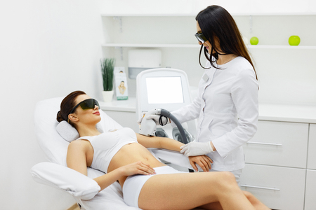 Photo for Woman Beauty. Beautician Doing Epilation On Beautiful Girl's Body In Medical Center. Female Receiving Laser Light Hair Removal Treatment For Hairless Smooth Skin At Cosmetology Salon. High Resolution - Royalty Free Image