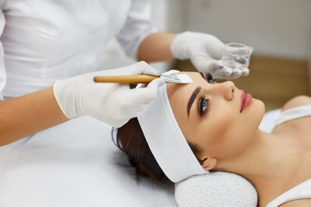 Photo pour Face Skin Care. Beautician Applying Beauty Oil Mask On Face Using Brush In Spa Salon. Closeup Of Female Client Getting Hydrating Procedure In Beauty Clinic. Cosmetology. High Resolution - image libre de droit