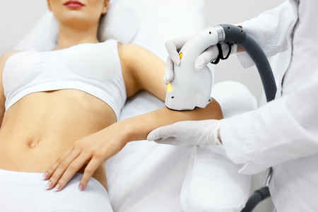Photo pour Cosmetology. Closeup Of Beautician Doing Laser Epilation Treatment On Beautiful Female Body, Removing Hair On Silky Skin. Woman Receiving Light Hair Removal Procedure In Beauty Salon. High Resolution - image libre de droit