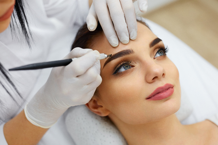 Photo for Make-Up. Beautician Hands Doing Eyebrow Tattoo On Woman Face.Permanent Brow Makeup In Beauty Salon. Closeup Of Specialist Doing Eyebrow Tattooing For Female. Cosmetology Treatment. High Resolution - Royalty Free Image