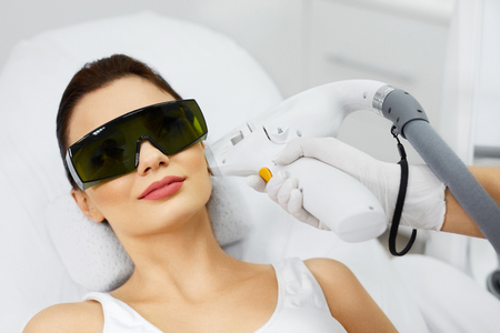 Photo pour Light Hair Removal. Closeup Of Beautiful Young Woman At Spa Clinic Receiving Face Treatment. Attractive Female Getting Laser Skin Procedures At Beauty Salon. Beauty Care. High Resolution - image libre de droit