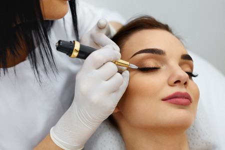 Photo pour Beauty Woman Face. Beautiful Girl Receiving Permanent Make-Up From Beautician. Closeup Of Young Female Getting Eyelid Tattoo At Spa Salon. Makeup And Cosmetics. Cosmetology. High Resolution - image libre de droit