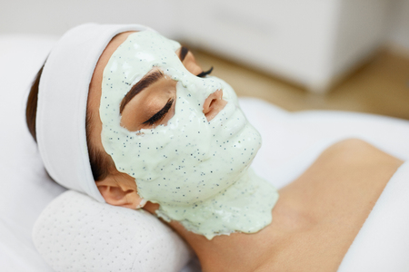 Photo pour Woman Skin Care. Closeup Of Beautiful Girl With Cosmetic Mask On Facial Skin In Beauty Salon. Young Female With Face Covered With Green Moisturizing Alginate Mask. Beauty Treatment. High Resolution - image libre de droit