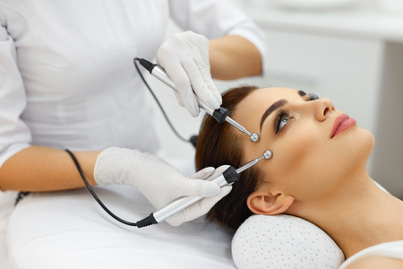 Photo pour Facial Skin. Closeup Of Beautiful Woman Receiving Facial Microcurrent Treatment From Therapist At Spa Salon. Beautician Using Electrical Impulses For Facial Procedures. Cosmetology. High Resolution - image libre de droit