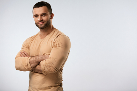Foto de Handsome Man Portrait. Closeup Of Strong Sexy Young Male With Beautiful Face, Fit Muscular Body Standing With HIs Arms Crossed. Attractive Confident Guy On Grey Background. High Resolution - Imagen libre de derechos