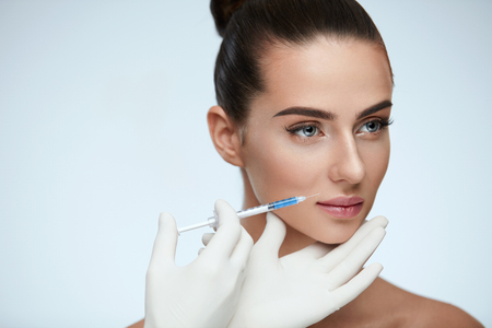 Photo pour Plastic Surgery. Closeup Of Beautician Hands Holding Syringe Near Female Facial Skin Doing Injections. Portrait Of Beautiful Young Woman Face Getting Hyaluronic Injection. Cosmetology. High Resolution - image libre de droit