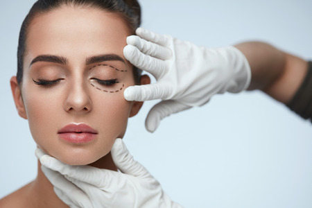 Foto de Facial Treatment. Portrait Of Beautiful Sexy Woman With Closed Eyes And Black Surgical Lines On Skin. Closeup Of Hands Touching Young Female Face. Plastic Surgery Concept. High Resolution - Imagen libre de derechos
