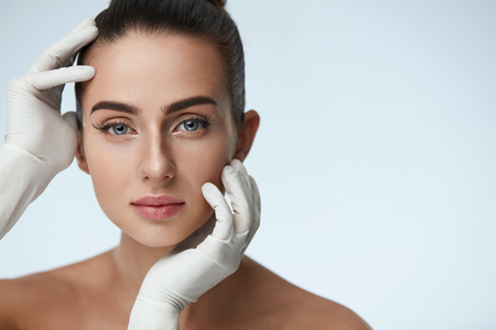 Photo pour Cosmetology. Portrait Of Beautiful Woman Before Plastic Surgery Operation With Hands In Gloves Touching Her Beauty Face. Closeup Of Healthy Young Female With Soft Smooth Facial Skin. High Resolution - image libre de droit