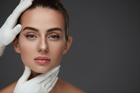 Photo pour Beauty Woman Face. Portrait Beautiful Girl With Perfect Makeup And Smooth Soft Healthy Skin. Closeup Of Cosmetician Hands In Gloves Touching Young Woman Facial Skin. Plastic Surgery. High Resolution - image libre de droit