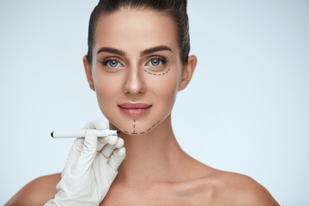 Foto de Beauty Operation. Closeup Of Beautician Hand Drawing Surgical Lines On Beautiful Young Woman Face. Portrait Of Sexy Woman With Soft Skin Before Plastic Surgery. Facial Treatment. High Resolution - Imagen libre de derechos