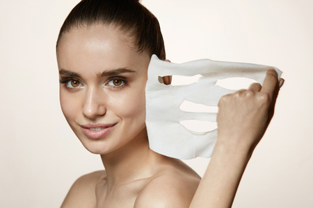 Photo pour Face Skin Care. Portrait Of Beautiful Smiling Girl Removing White Sheet Mask From Healthy Fresh Skin. Closeup Of Attractive Sexy Woman With Natural Makeup And Mask On Facial Skin. High Resolution - image libre de droit