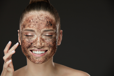 Photo pour Face Skin Scrub. Portrait Of Sexy Smiling Female Model Applying Natural Coffee Mask, Face Scrub On Facial Skin. Closeup Of Beautiful Happy Woman With Face Covered With Beauty Product. High Resolution - image libre de droit