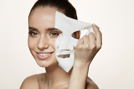 Photo pour Woman Beauty Face. Closeup Of Smiling Young Female With Fresh Natural Makeup Removing Textile Sheet Mask From Facial Skin. Portrait Of Attractive Happy Girl With White Cosmetic Mask. High Resolution - image libre de droit