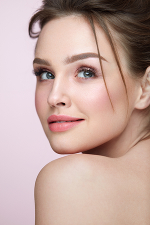 Photo for Beauty Woman Face. Closeup Of Beautiful Young Female Model With Fresh Natural Skin And Professional Facial Makeup On Pink Background. Portrait Of Sexy Girl With Glamour Hair Style. High Resolution - Royalty Free Image