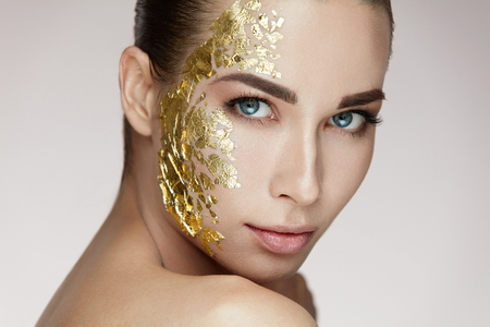 Photo for Beauty Woman Face. Closeup Of Beautiful Healthy Girl With Cosmetic Gold Mask On Soft Smooth Skin. Portrait Of Young Female With Natural Makeup Doing Skin Care Procedure. Cosmetics. High Resolution - Royalty Free Image