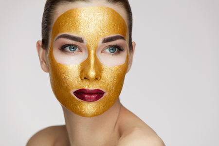 Photo for Beauty Cosmetics. Closeup Of Healthy Young Woman With Gold Cosmetic Face Mask On Soft Skin. Portrait Of Beautiful Sexy Female Model With Face Product On Fresh Skin. Facial Care. High Resolution - Royalty Free Image