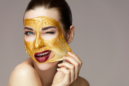 Photo pour Woman Face Beauty. Closeup Beautiful Sexy Girl Taking Off Cosmetic Peeling Gold Mask From Healthy Skin. Portrait Of Attractive Young Female With Bright Makeup Removing Beauty Product. High Resolution - image libre de droit