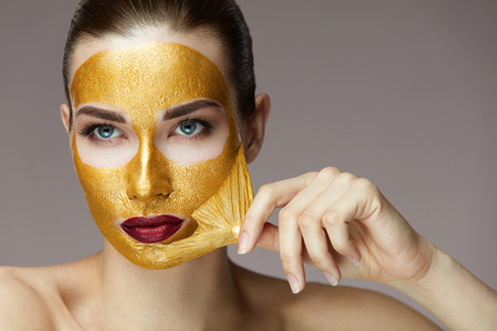 Photo pour Beauty Product. Portrait Of Sexy Healthy Girl Removing, Peeling Cosmetic Gold Mask From Beautiful Face Skin. Closeup Of Attractive Young Woman With Fresh Skin And Bright Makeup. High Resolution - image libre de droit