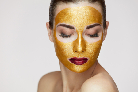 Foto de Beauty Cosmetics. Closeup Of Healthy Young Woman With Gold Cosmetic Face Mask On Soft Skin. Portrait Of Beautiful Sexy Female Model With Face Product On Fresh Skin. Facial Care. High Resolution - Imagen libre de derechos