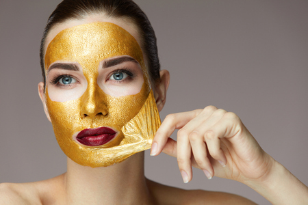 Foto de Beauty Product. Portrait Of Sexy Healthy Girl Removing, Peeling Cosmetic Gold Mask From Beautiful Face Skin. Closeup Of Attractive Young Woman With Fresh Skin And Bright Makeup. High Resolution - Imagen libre de derechos