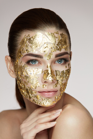 Photo pour Spa Procedure. Portrait Of Sexy Girl With Gold Mask On Facial Skin Caressing Body. Closeup Of Attractive Woman With Smooth Skin And Cosmetic Product On Face. Beauty Concept. High Resolution - image libre de droit