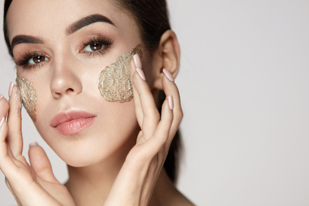 Foto de Woman Face Skin Care. Closeup Beautiful Young Female Model With Natural Makeup Applying Scrub On Face. Portrait Of Attractive Girl Touching Soft Facial Skin With Cosmetic Product On. High Resolution - Imagen libre de derechos