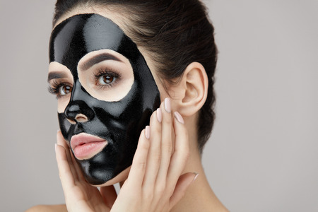 Photo pour Woman Beauty Face Skin Care. Closeup Of Attractive Girl Applying Black Smooth Peeling Mask On Facial Skin. Portrait Of Beautiful Female With Natural Makeup And  Cosmetic Peel Off Mask. High Resolution - image libre de droit