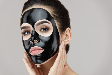 Photo pour Woman Face With Black Peeling Mask On Skin. Portrait Of Beautiful Young Female Applying Cosmetic Mask On Face. Closeup Of Attractive Girl Model With Skin Care Product On Facial Skin. High Resolution - image libre de droit